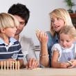 Family playing dominoes — Stock Photo