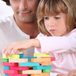Stock Photo: Father and daughter building tower of blocks