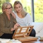 žena ukazující její vnučka, jak malovat — Stock fotografie