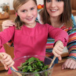 Mother and daughter making a salad — Stock Photo