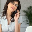 Woman working at a laptop while talking on the telephone — Stock Photo