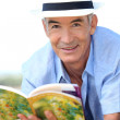 Old man reading a book - Stock Photo