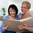 Stock Photo: Two women looking through photo album