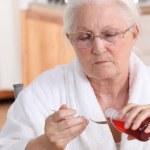 Senior woman taking cough syrup — Stock Photo