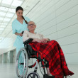 Stock Photo: Nurse and old lady in wheelchair