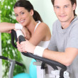 Stock Photo: Two young resting on cardio machines
