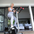 Senior woman on an exercise bike — Stock Photo