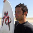 Man with a surf board — Stock Photo