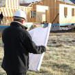 Construction site supervisor looking at a blueprint - Stock Photo