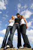 Three woman stood on large rock at the beach — Stock Photo