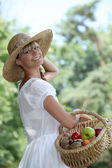 Summery woman in a straw hat holding a basket of fruit — Stock Photo