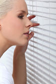 Blond woman peering through window blind — Stock Photo