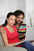 Couple at home using a laptop computer — Stock Photo