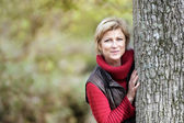 Timid woman hiding behind a tree — Stock Photo