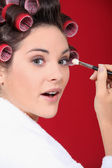 Woman with curlers in her hair putting make up — Stock Photo