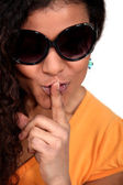 Woman wearing sunglasses making shush gesture — Stock Photo