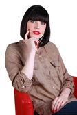 žena sedí v červené křeslo uvažuje o fotoaparát — Stock fotografie