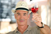 Old man raising a glass of claret — Stock Photo