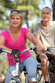 60 years old man and woman doing bike — Stock Photo