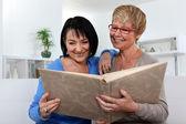 Two women looking through photo album — Stock Photo