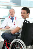 A doctor and a patient in wheelchair — Stock Photo