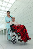 A nurse and an old lady in wheelchair — Stock Photo