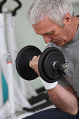 Mature white-haired man lifting weight in sports room — Stock Photo