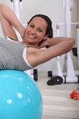 Woman doing sit-ups on gym ball — Stock Photo