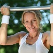 Stock Photo: Blond womexercising on pull-up bar outdoors