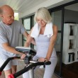 Man helping his wife use an exercise machine — Stock Photo