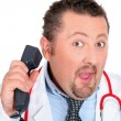 图库照片: Funny doctor with a telephone