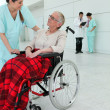 Woman in wheelchair taken care of — Stock Photo