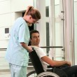 Nurse and patient in wheelchair in front of a lift — Stock Photo