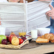 Stock Photo: Couple reading newspaper during breakfast