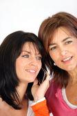 两个女人站和聆听一段手机通话 — 图库照片