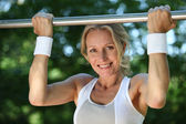 Blond woman exercising on pull-up bar outdoors — Stock Photo