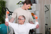 Senior woman working out with a personal trainer — Stock Photo