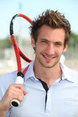Male tennis player holding racquet over shoulder — Stock Photo
