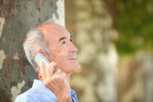 Grey-haired man with mobile telephone stood by tree — Stock Photo