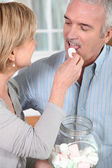 Senior woman giving a bonbon to her husband — Stock Photo
