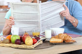 Couple reading newspaper during breakfast — Stock Photo