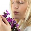 Close-up shot of blonde eyes shut smelling bunch of flowers — Stock Photo #8530357