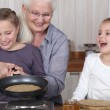 Grandmother and granddaughters making pancakes — Stock Photo