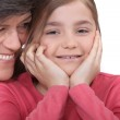 Little girl sitting with her grandmother — Stock Photo