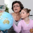 Woman looking at a globe with her granddaughter — Stock Photo