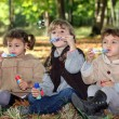 Young children blowing bubbles in the woods — Stock Photo