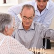 Young man watching an older couple play chess — Stock Photo