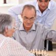 Stock Photo: Young mwatching older couple play chess