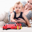 Young womplaying with little boy and his toys — Stock Photo #8531086