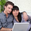 A couple on a couch doing computer — Stock Photo